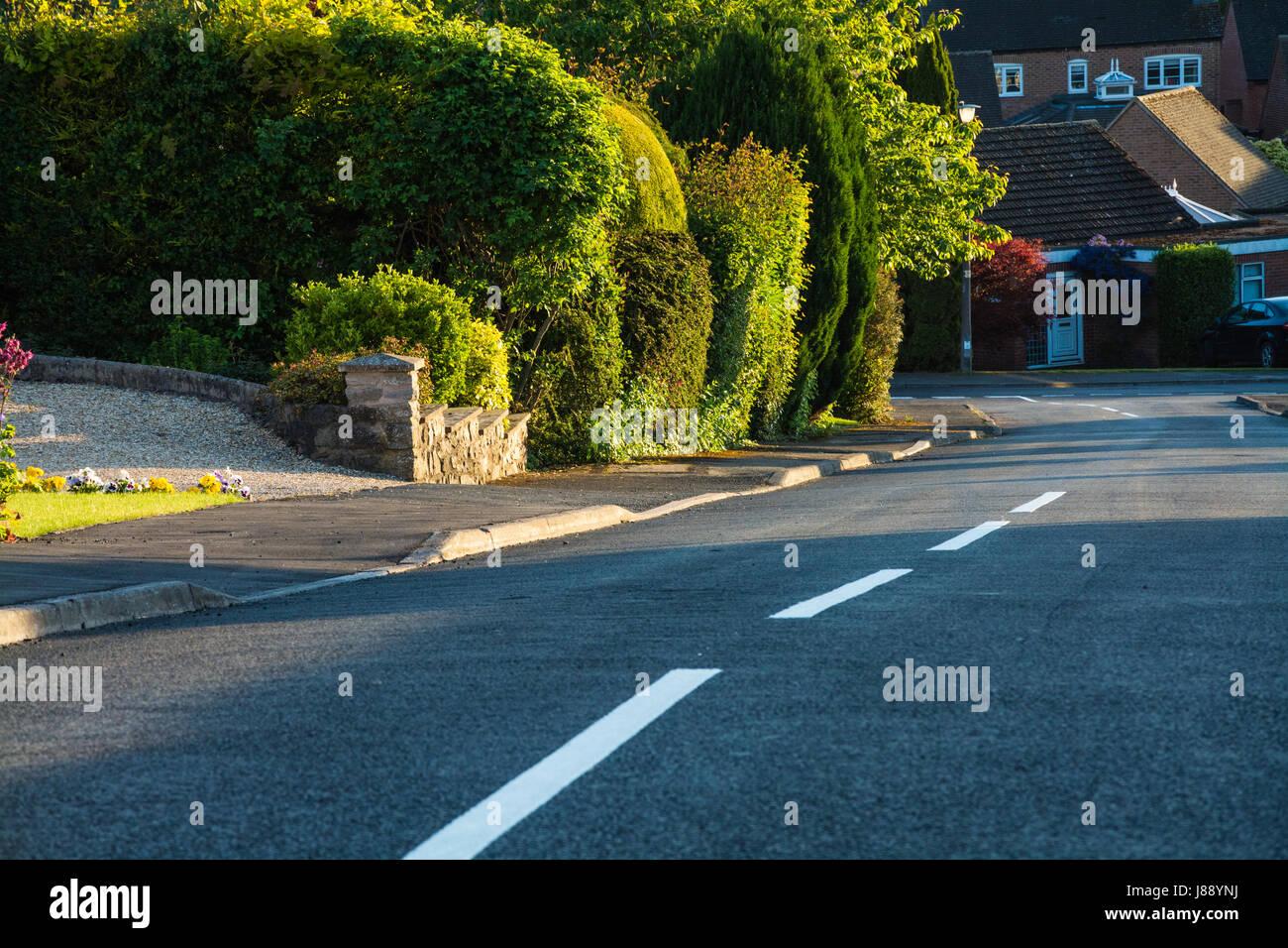 Rue de banlieue au crépuscule. La pente descendante. Le marquage routier. Shropshire, England, UK. Photo Stock