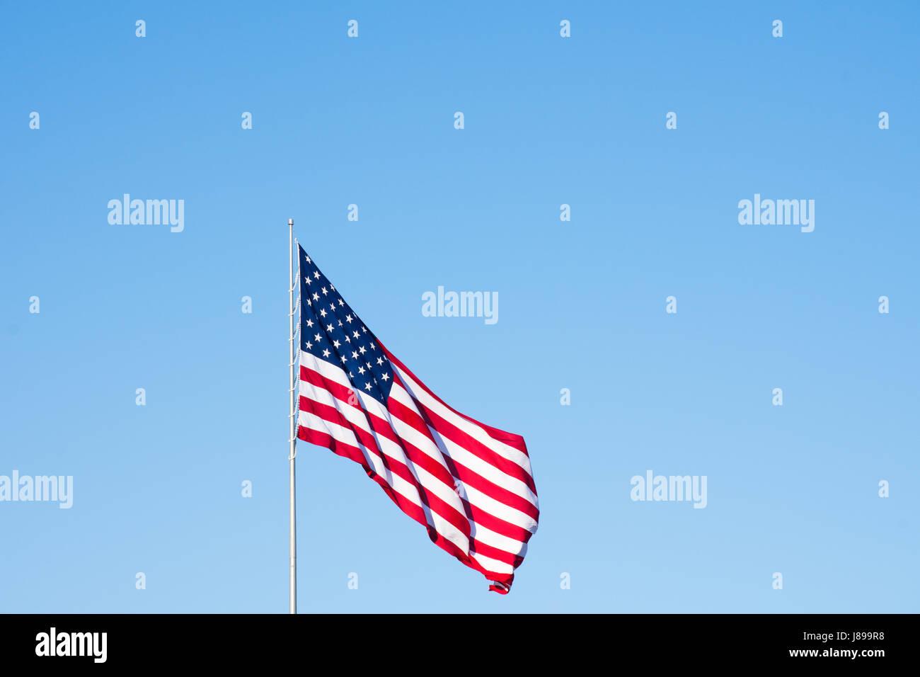 Drapeau américain déployé dans la brise contre un ciel sans nuages bleu moyen. A l'image exemplaire Photo Stock