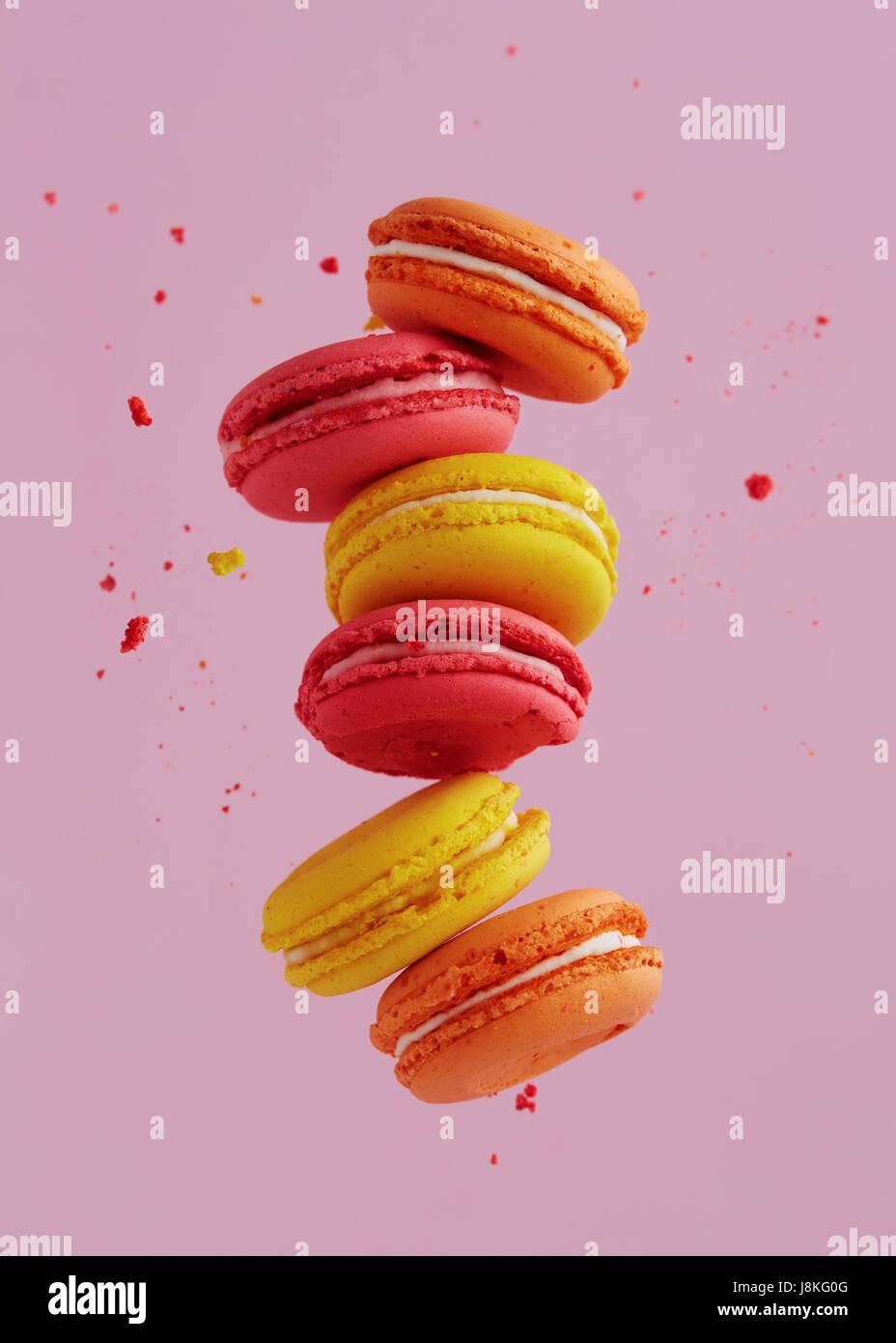 Différents types de macarons dans motion relevant sur fond rose. Doux et coloré qui tombent ou qui volent Photo Stock