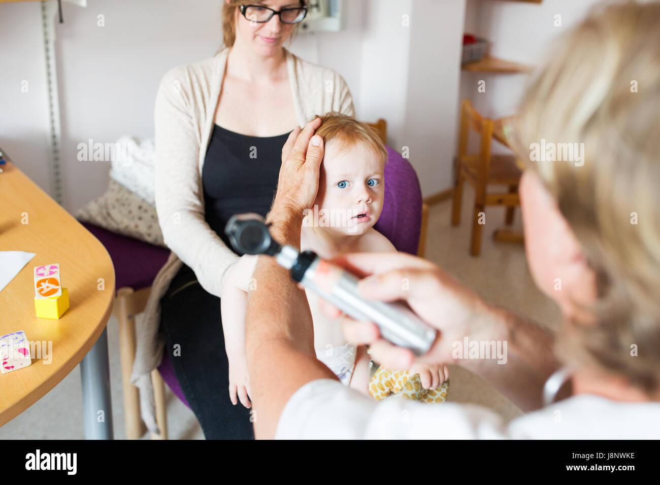Baby (12-17 mois) avec la mère et le médecin de salle d'examen Banque D'Images