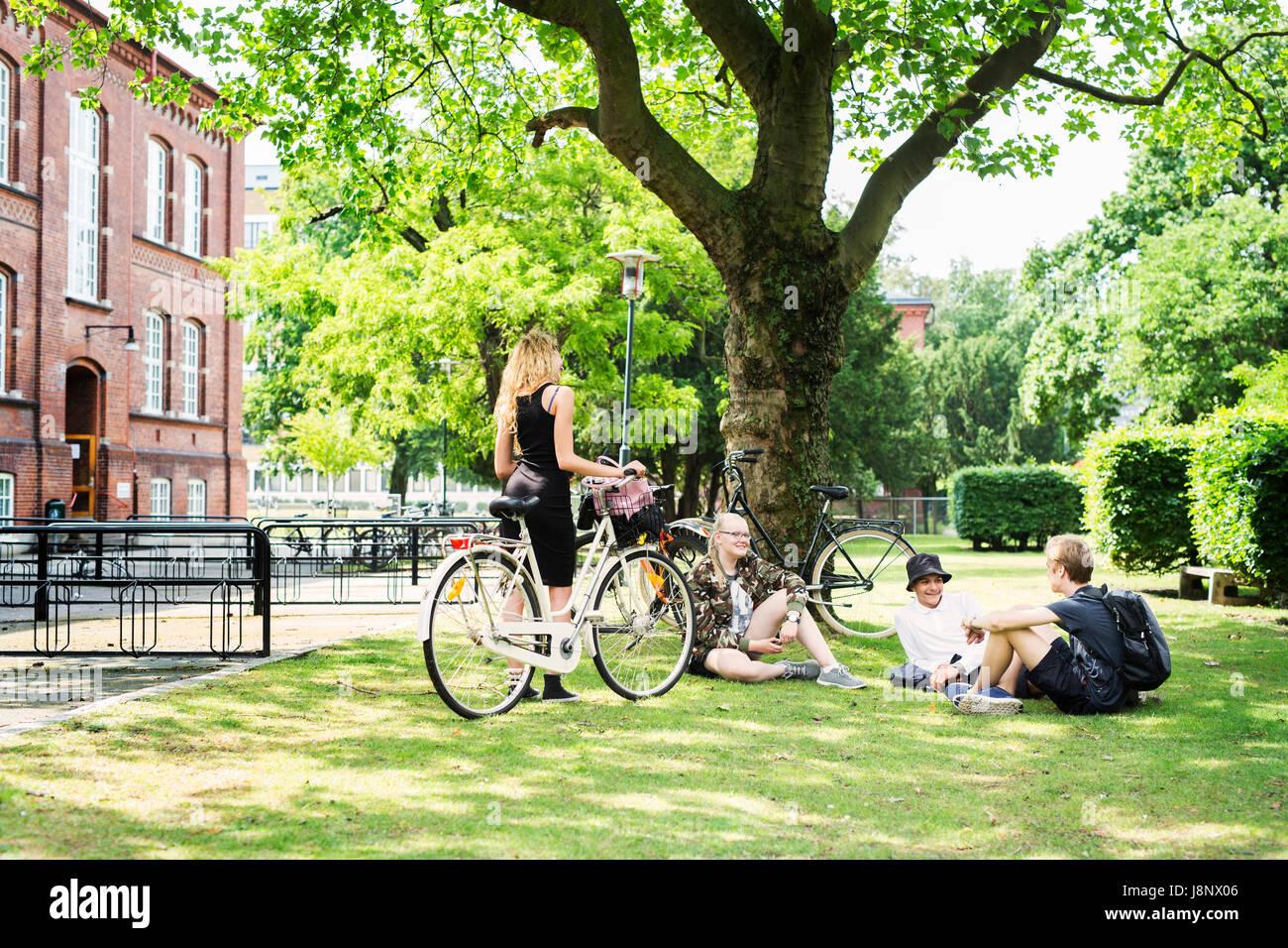 Étudiants (14-15) sitting on grass Banque D'Images