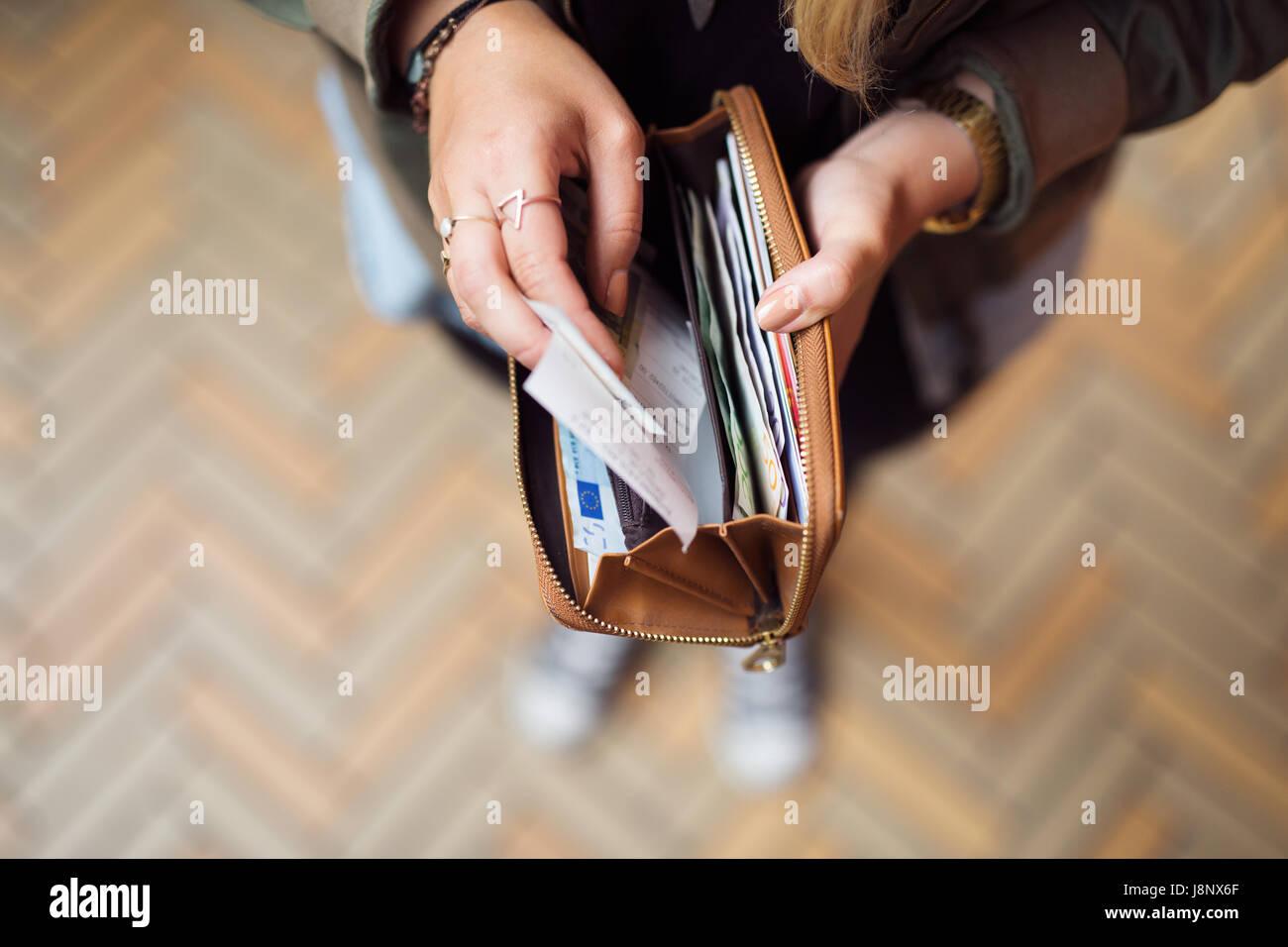 La tenue d'une femme avec porte-monnaie et des reçus de billets Banque D'Images