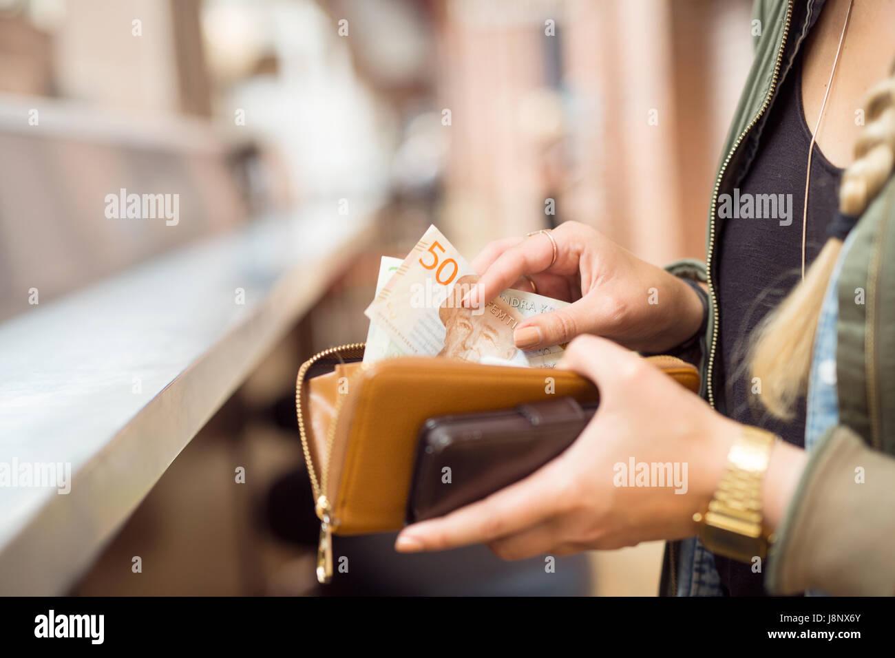 La tenue d'une femme avec porte-monnaie et billets cell phone Banque D'Images