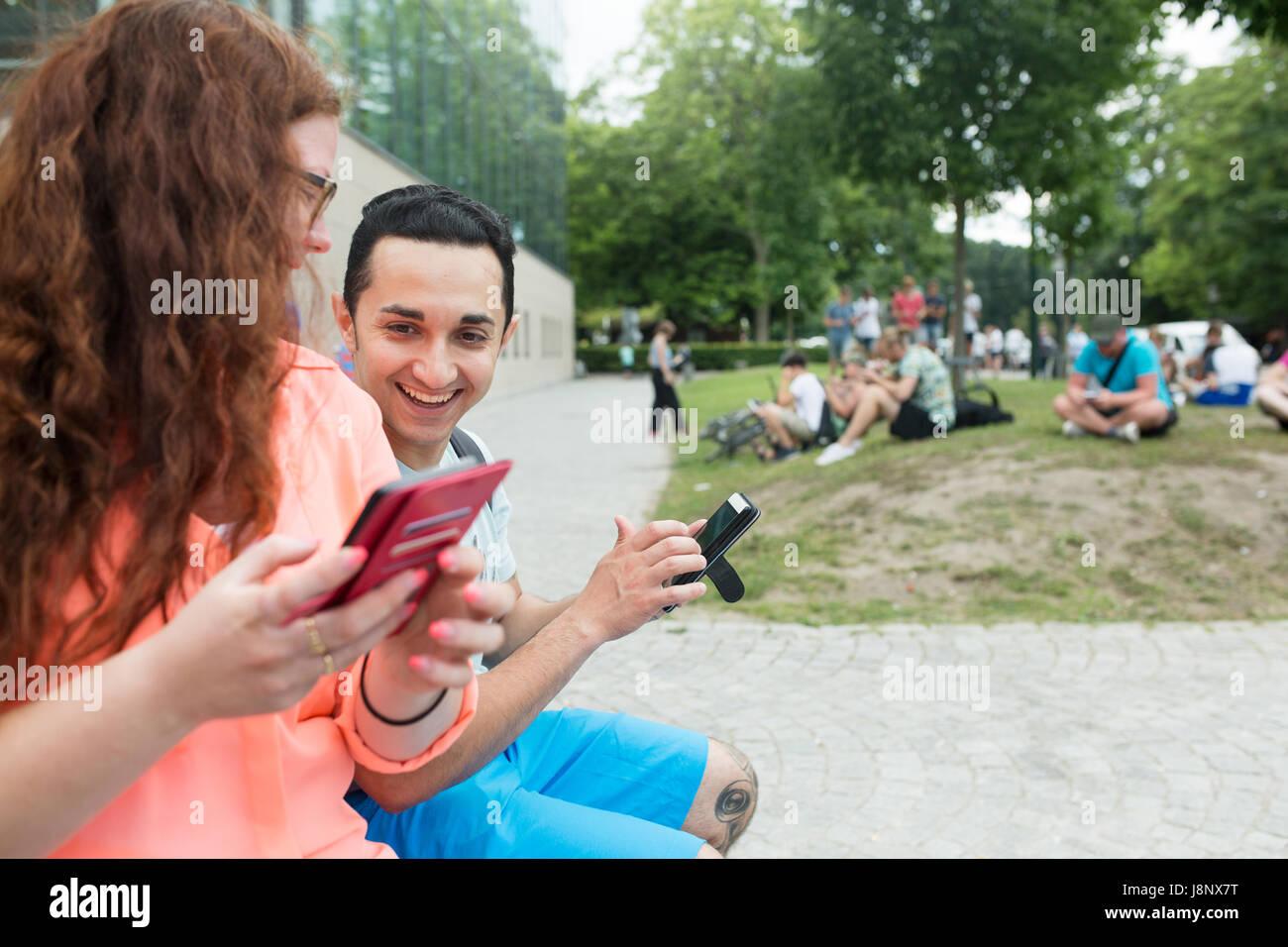Amis jouant le jeu de la réalité augmentée avec les téléphones mobiles Banque D'Images