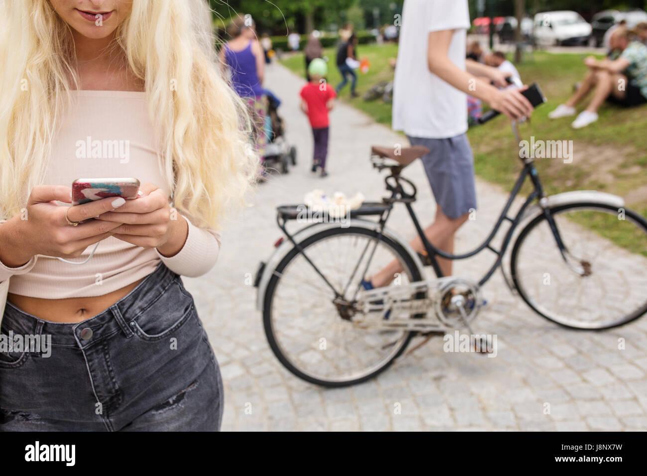 Teenage girl (16-17) en jouant avec le jeu de réalité augmentée mobile phone in park Banque D'Images