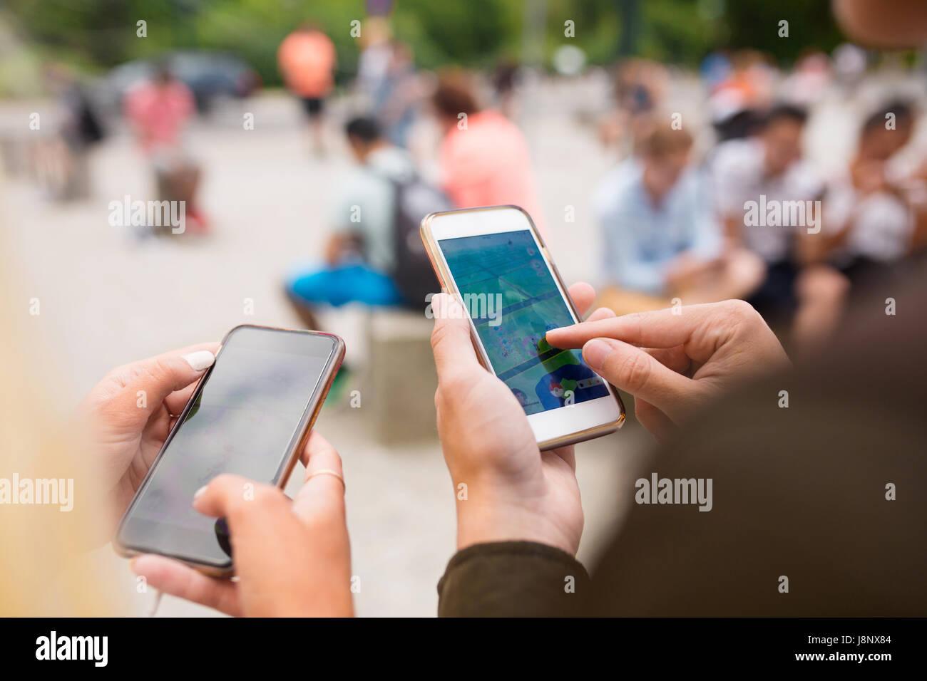Les personnes jouant le jeu de la réalité augmentée avec les téléphones mobiles Banque D'Images