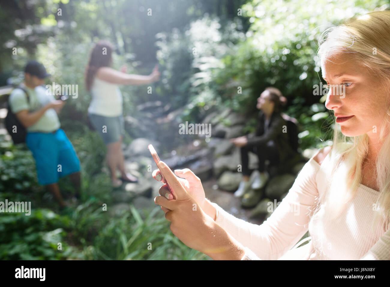 Groupe d'amis qui jouent le jeu de la réalité augmentée avec les téléphones mobiles dans le parc Banque D'Images