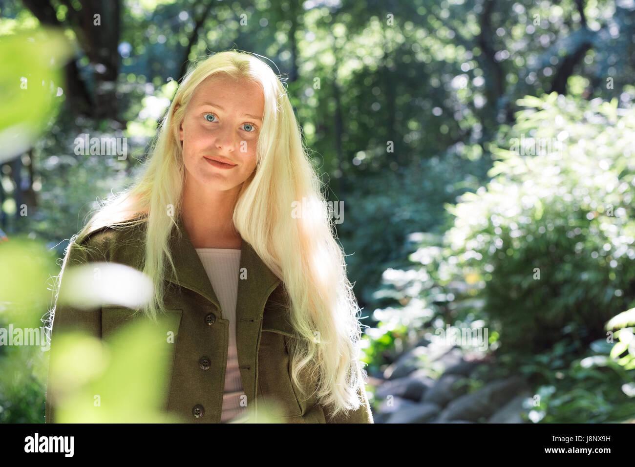 Teenage girl (16-17) entre les arbres dans le parc Banque D'Images