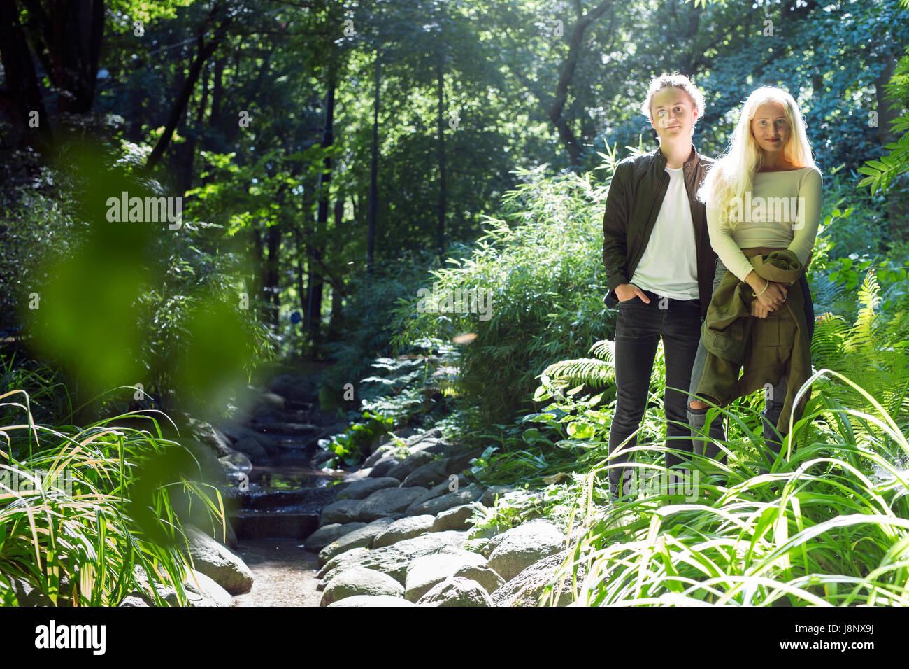 Couple (16-17) Comité permanent par stream in park Banque D'Images