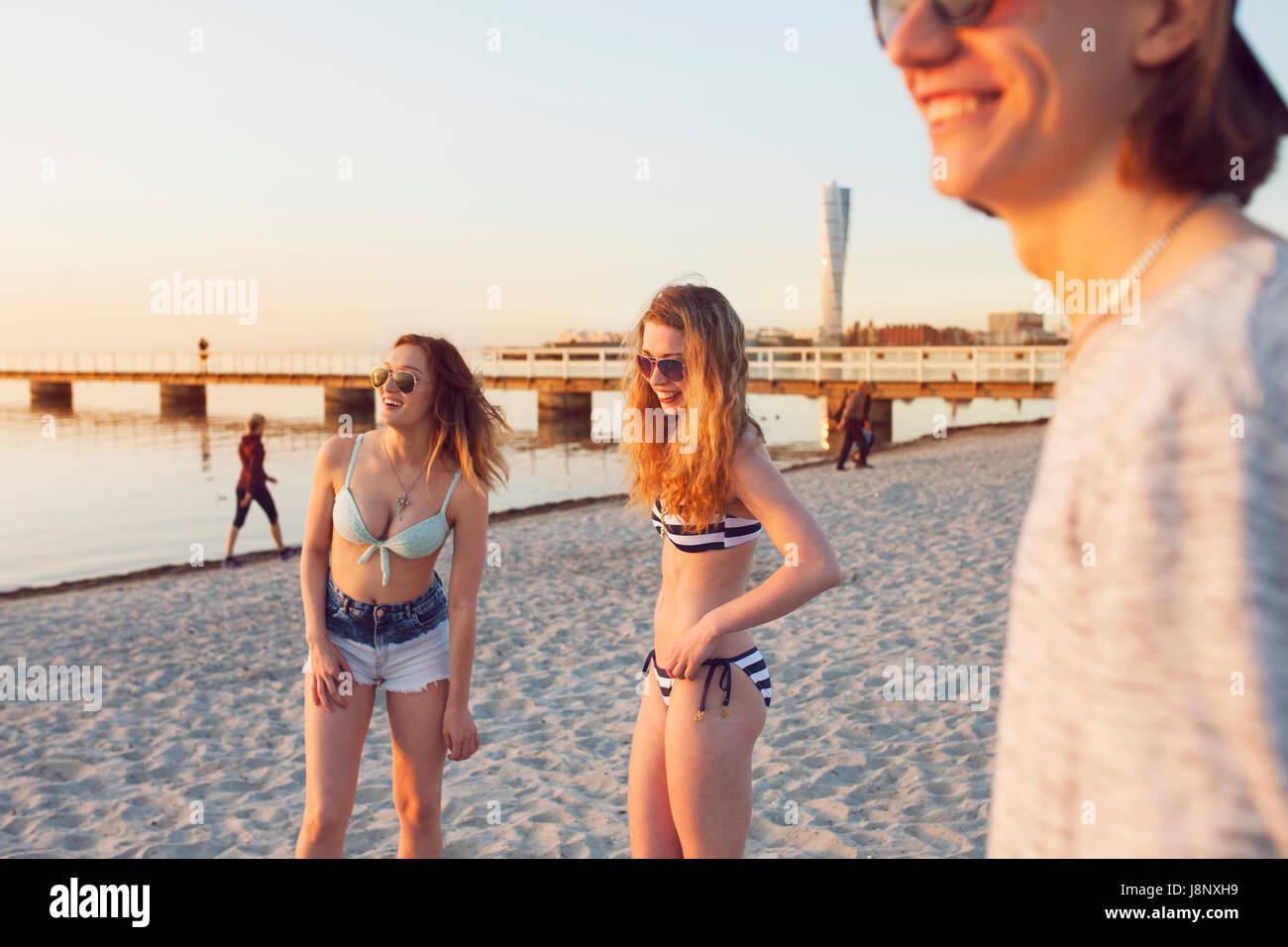 Jeune homme, jeune femme et teenage girl (16-17) smiling on beach Banque D'Images