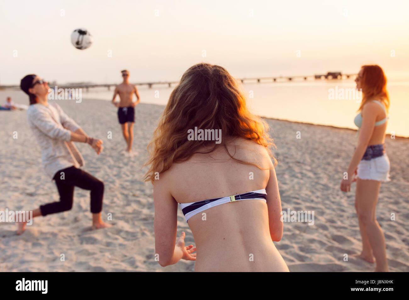 Les jeunes hommes, les jeunes femmes et teenage girl (16-17) jouer au volley-ball sur le sable au coucher du soleil Banque D'Images