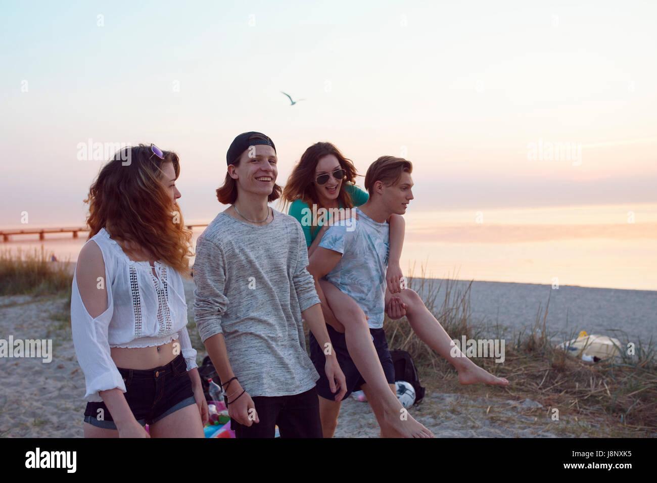 Les jeunes hommes, les jeunes femmes et teenage girl (16-17) walking on beach Banque D'Images