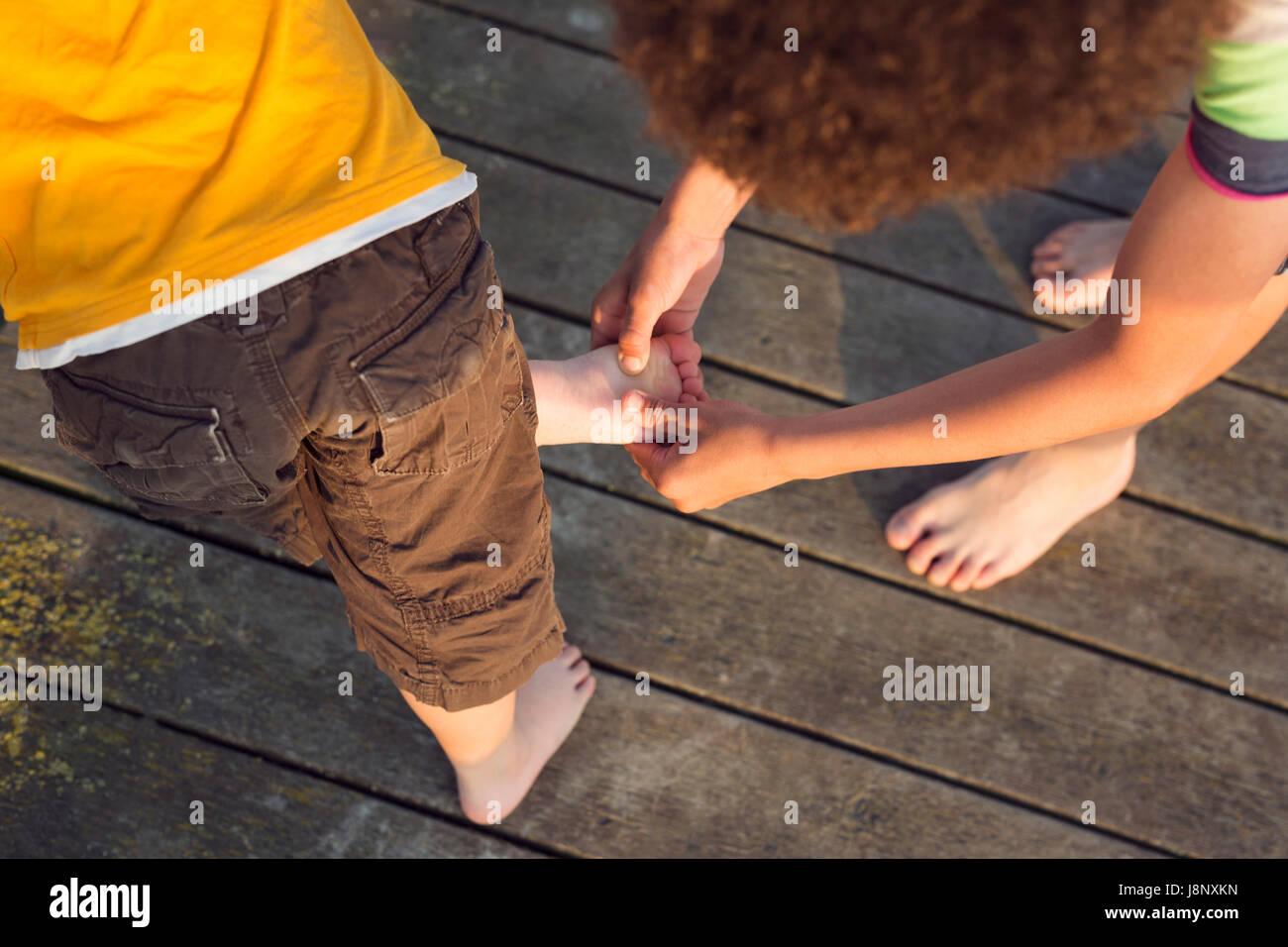Boy (10-11) L'examen d'autres boy's (4-5) foot Banque D'Images