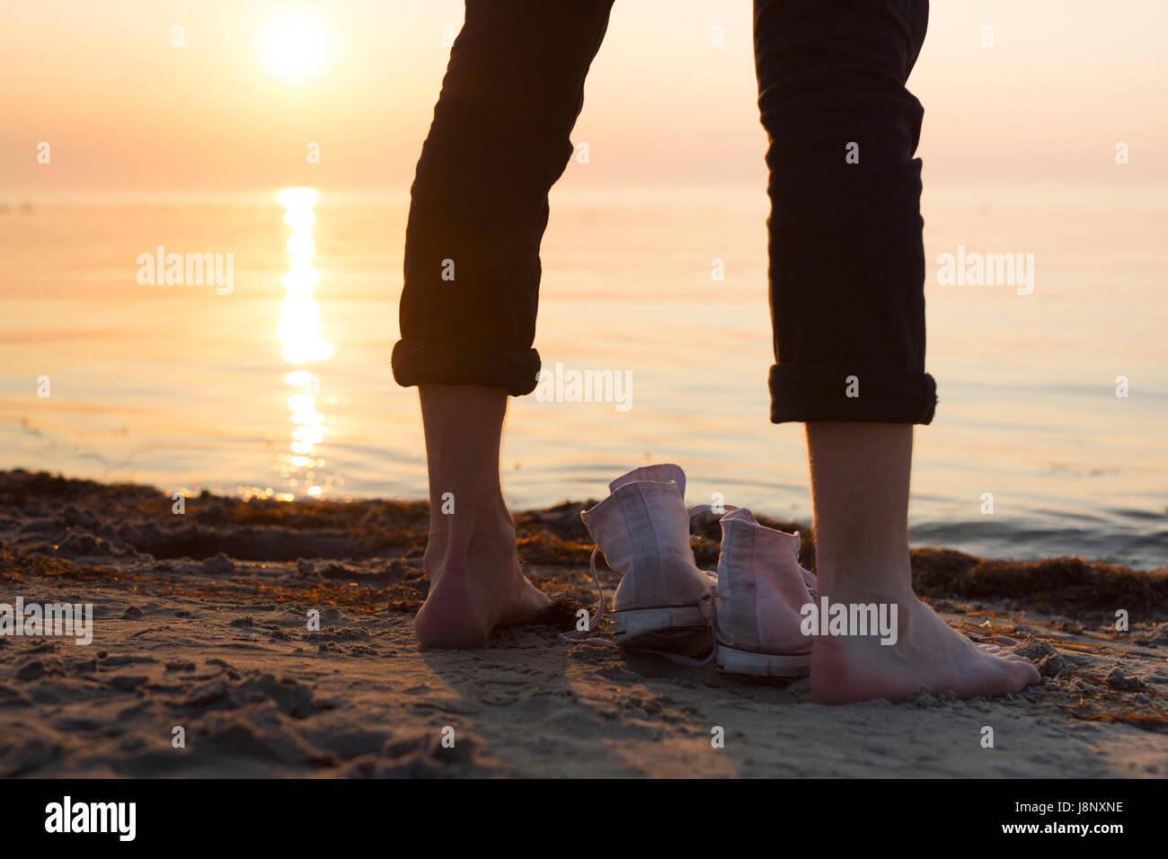 Homme debout par la mer au coucher du soleil Banque D'Images