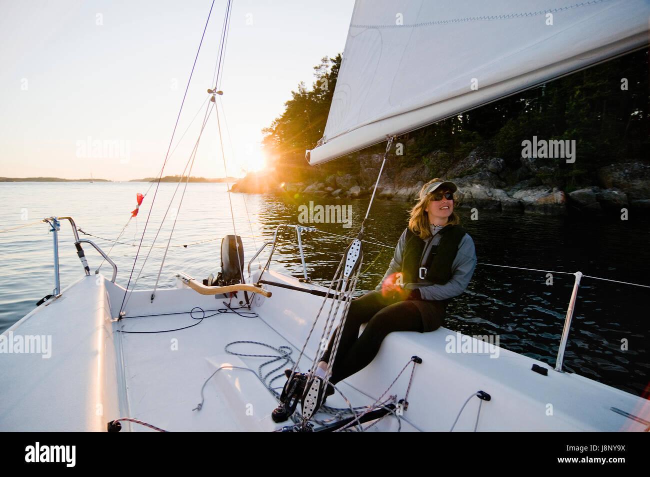 Femme assise sur voilier Banque D'Images