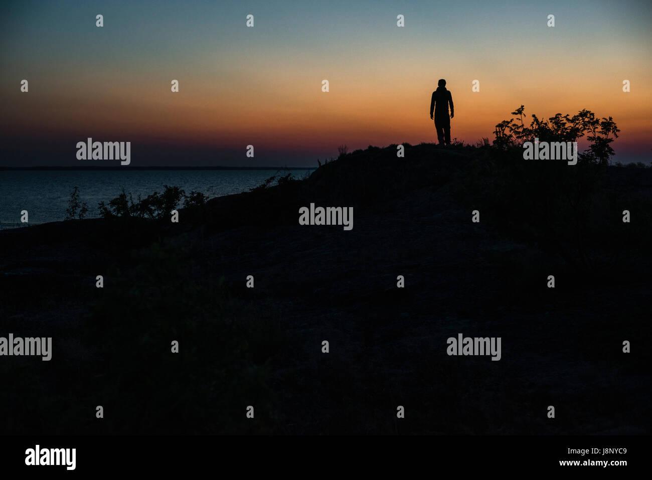 Silhouette of man au coucher du soleil Banque D'Images