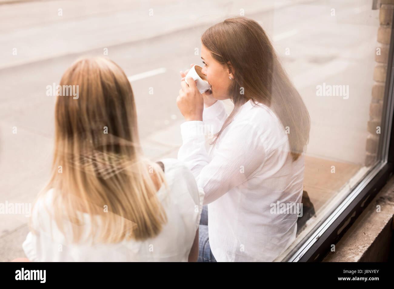 Les jeunes femmes de boire du café à l'extérieur de cafe Banque D'Images