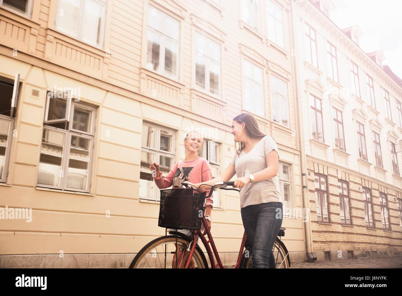 Les jeunes femmes marchant avec le vélo Banque D'Images