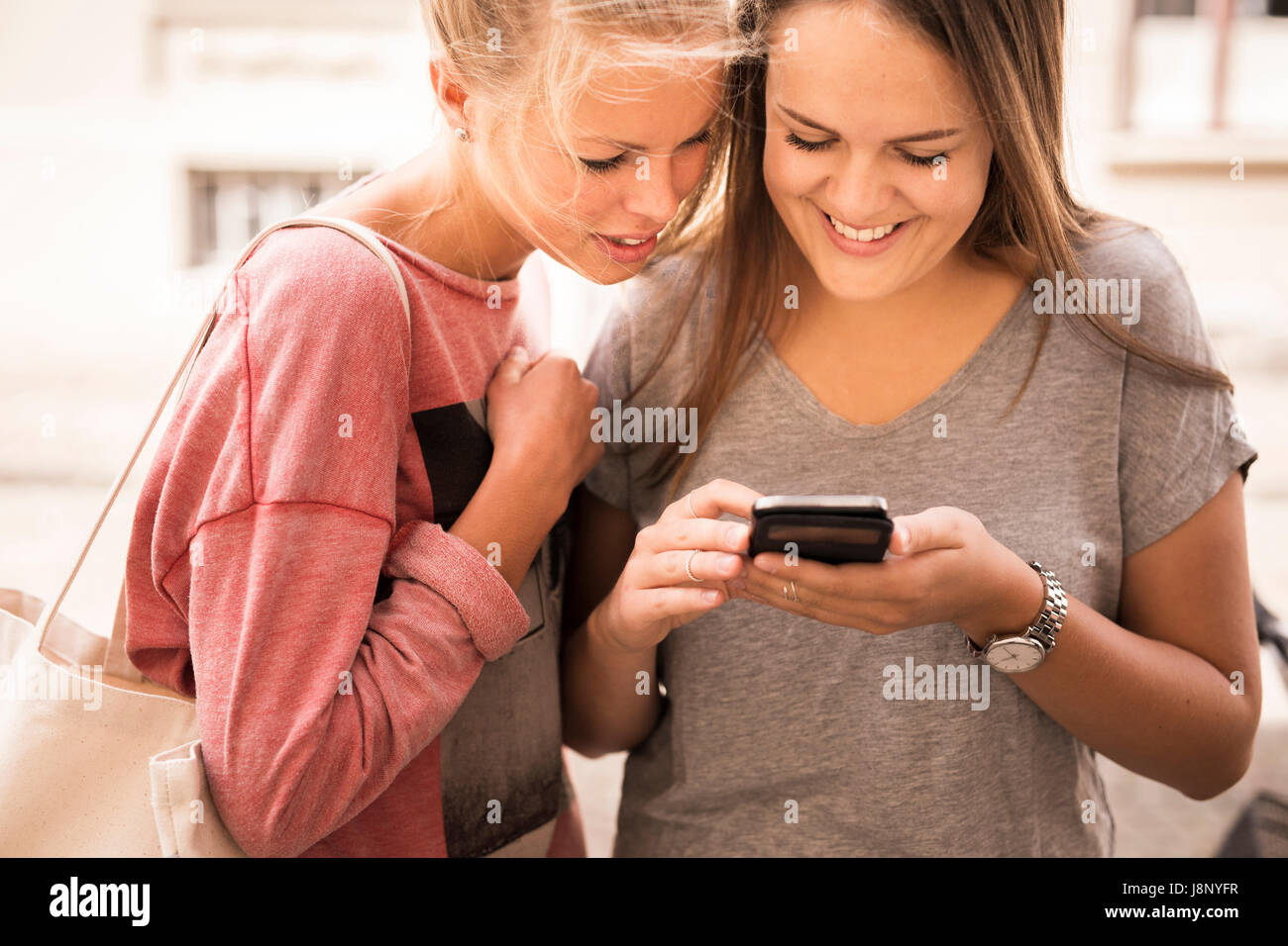 Smiling women using mobile phone Banque D'Images