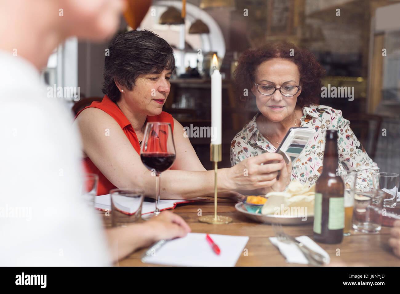 Businesswomen looking at mobile phone pendant le déjeuner au restaurant Banque D'Images