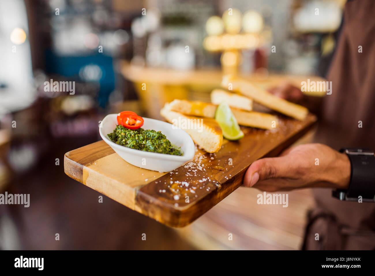 Waiter serving pain avec sauce pesto Banque D'Images