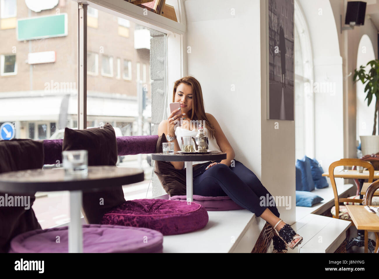 Businesswoman using mobile phone in restaurant Banque D'Images
