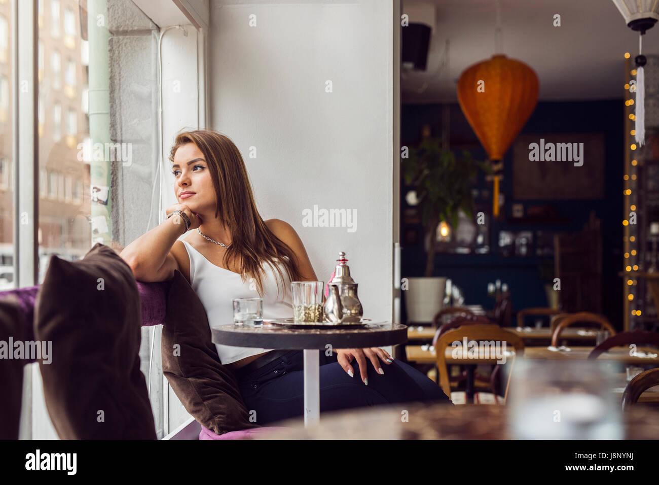 Businesswoman looking through window in restaurant Banque D'Images