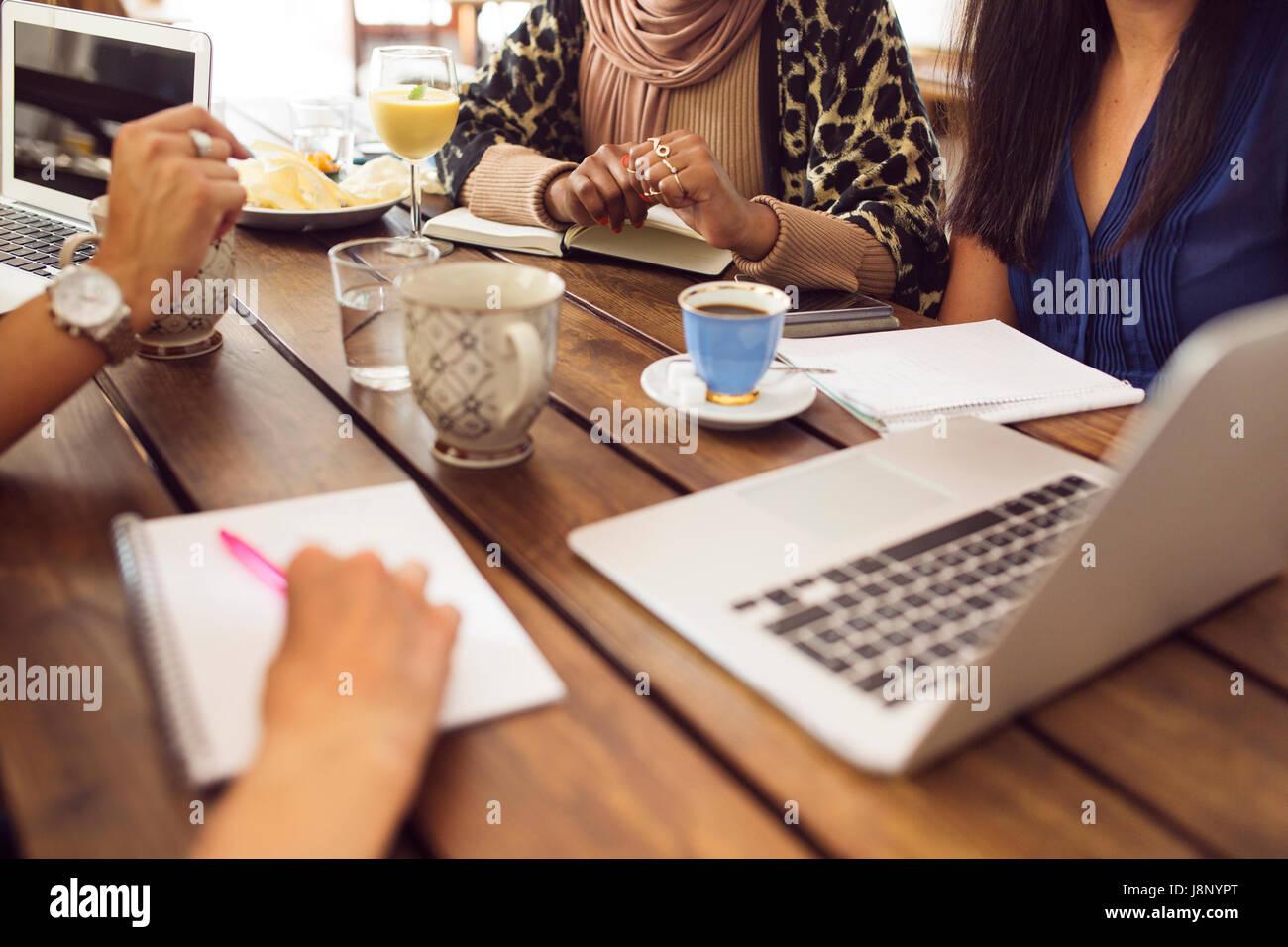 Businesswomen using laptop pendant le déjeuner au restaurant Banque D'Images