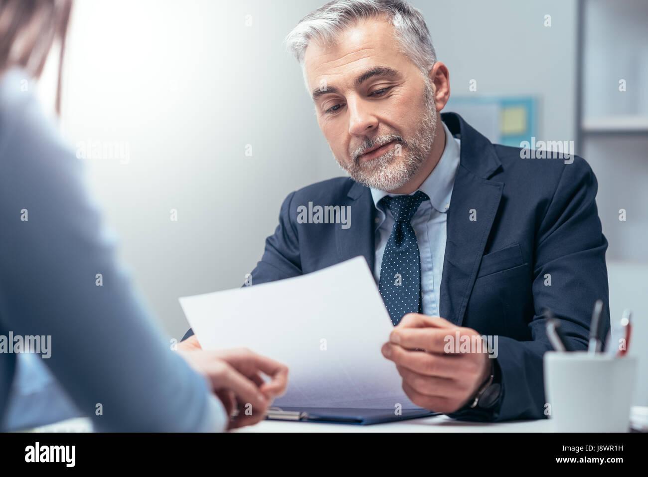 Jeune femme ayant un emploi entrevue avec un gestionnaire d'entreprise dans son bureau, il est l'examen de son curriculum Banque D'Images