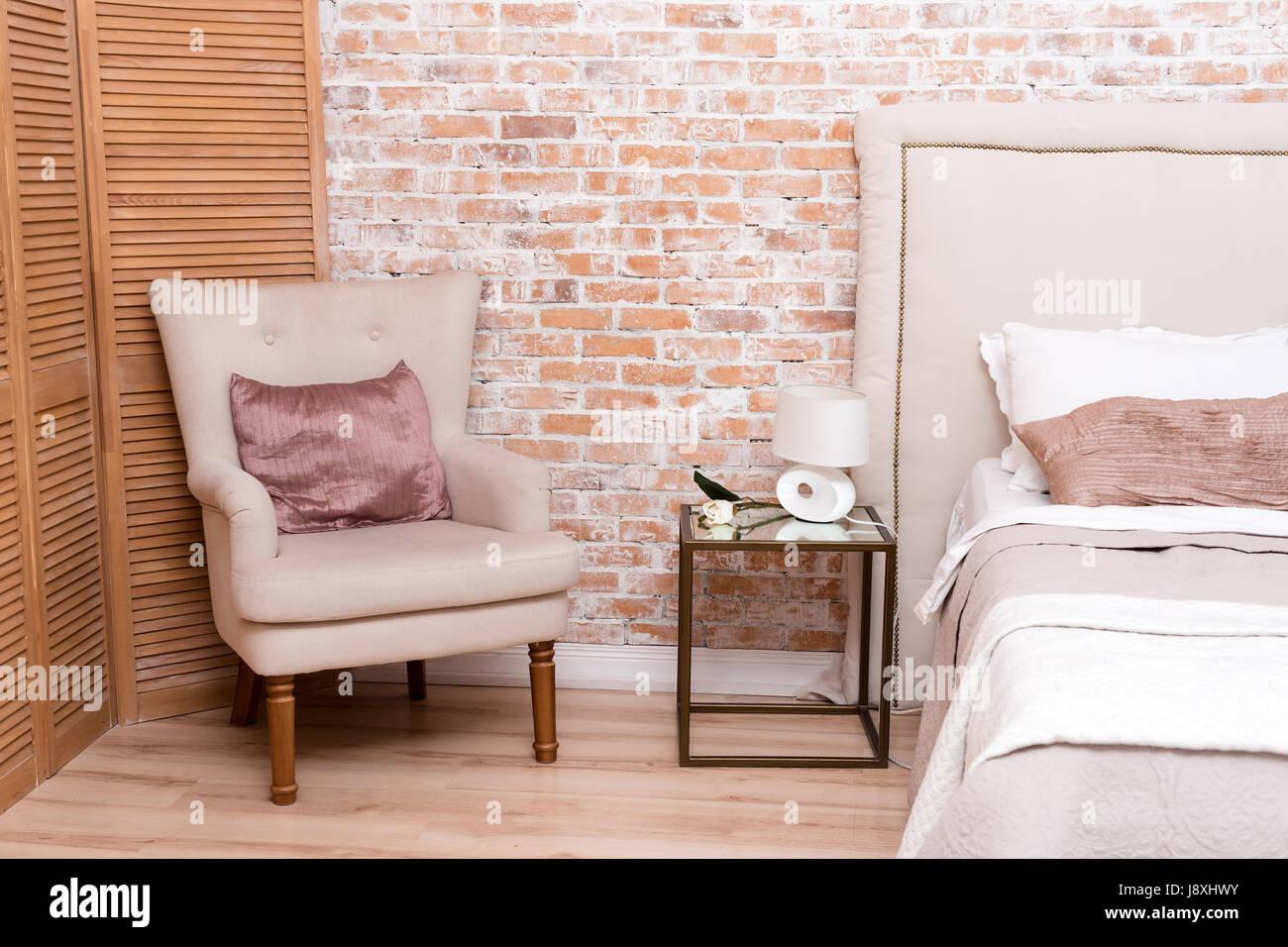 Belle chambre en mezzanine avec lit double et fauteuil près de mur ...