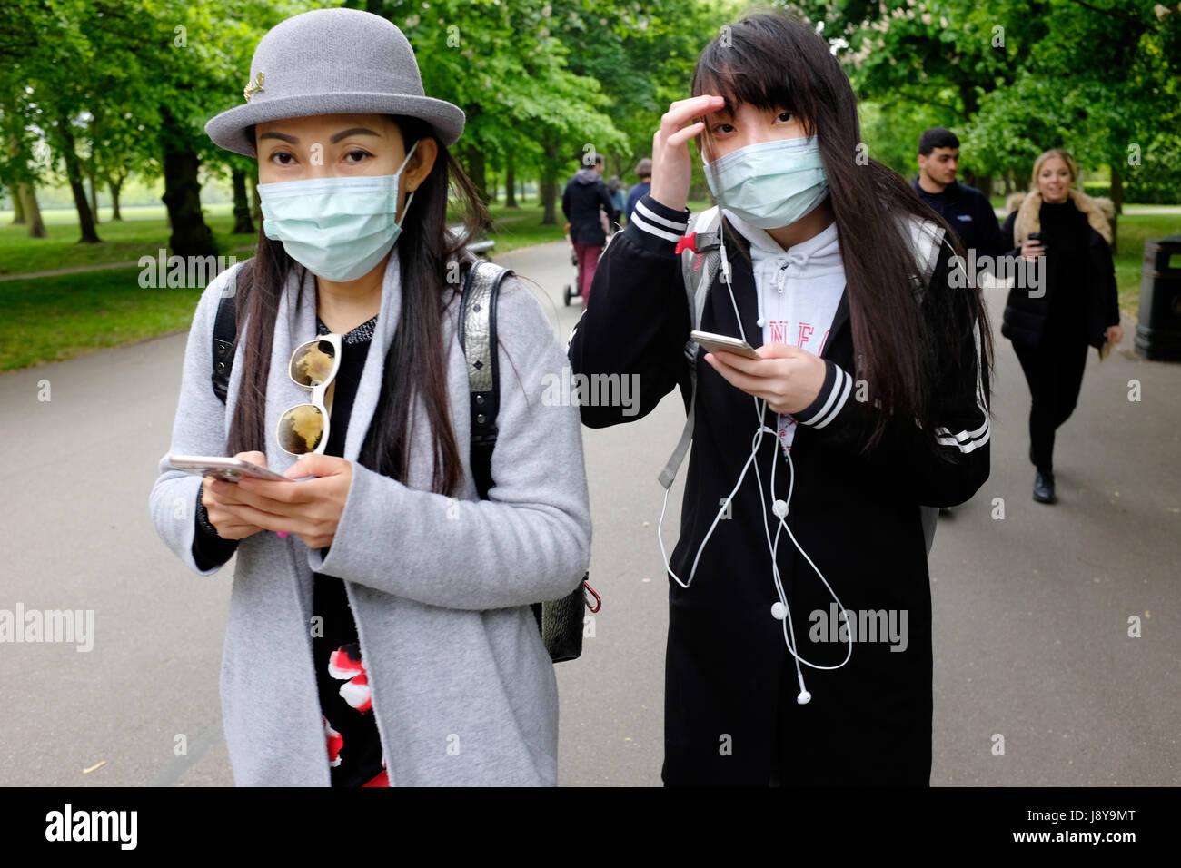 Deux jeunes femmes asiatiques portant des masques de la pollution dans un parc de Londres, Angleterre, Royaume-Uni. Photo Stock