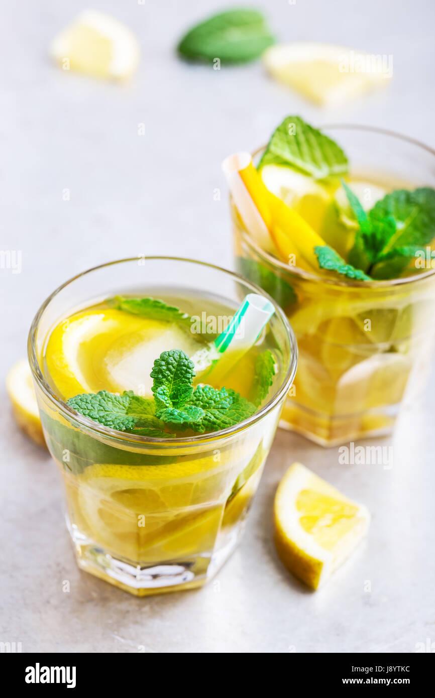 Citron glacé maison thé sucré à la menthe sur la table gris clair, rafraîchissements délicieux Photo Stock