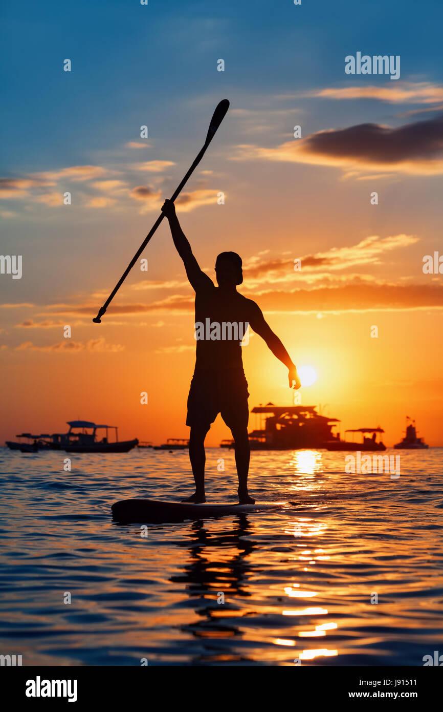 Paddle boarder. Coucher du soleil noir silhouette de jeune sportsman paddling on stand up paddleboard. Mode de vie Photo Stock