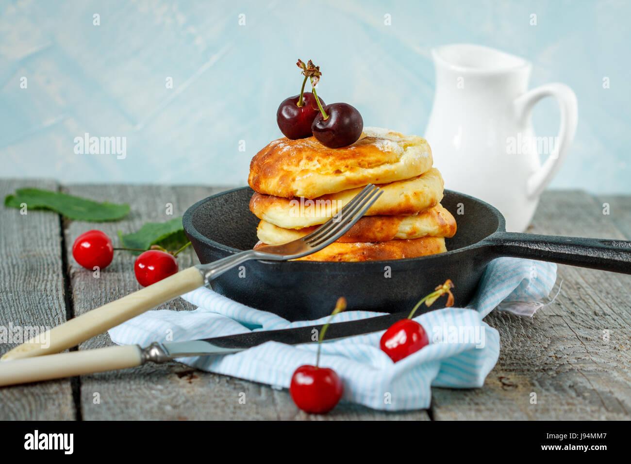 Des crêpes de fromage cottage avec les cerises dans une poêle en fonte. Fédération de dessert Photo Stock