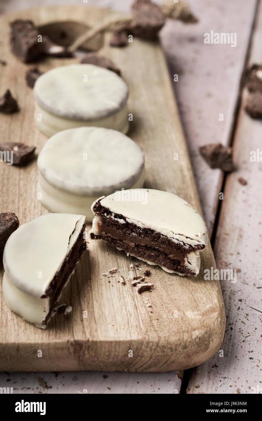 Certains argentine-uruguayen alfajores rempli de dulce de leche et recouverts d'une couche blanche sur une planche Photo Stock