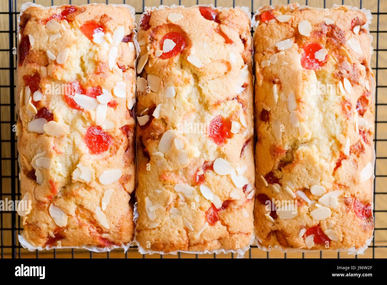Des plats maison. Trois gâteaux aux amandes et cerises sur une grille de refroidissement. Photo Stock