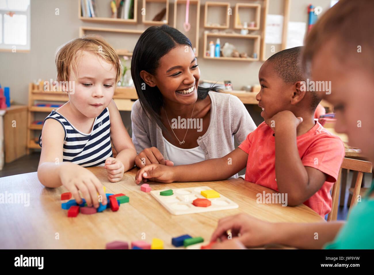 Les élèves et enseignants à l'aide de formes en bois dans l'école Montessori Photo Stock