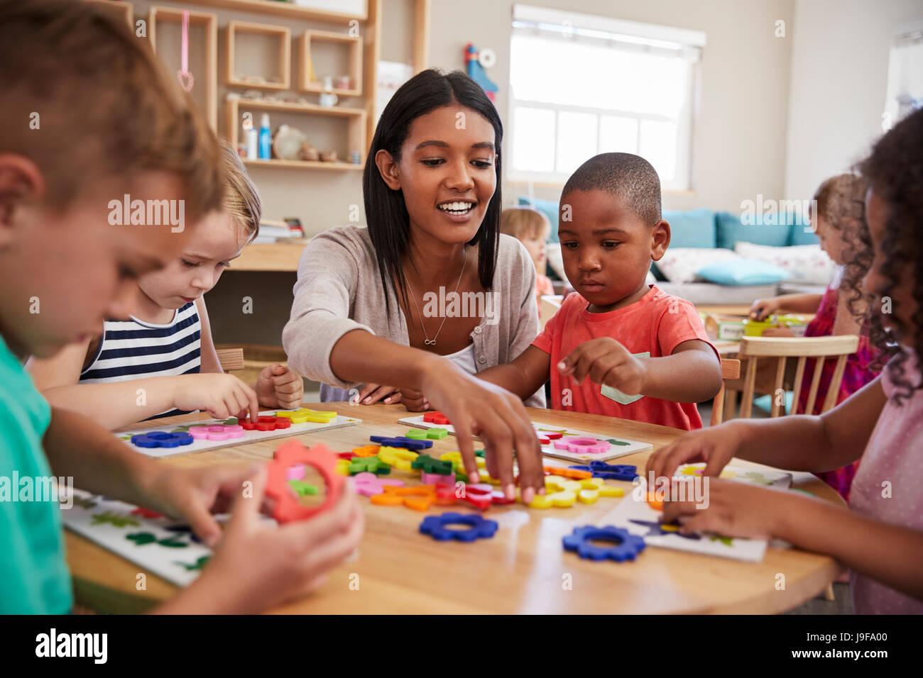 Les élèves et enseignants à l'aide de formes de fleurs en Montessori School Photo Stock
