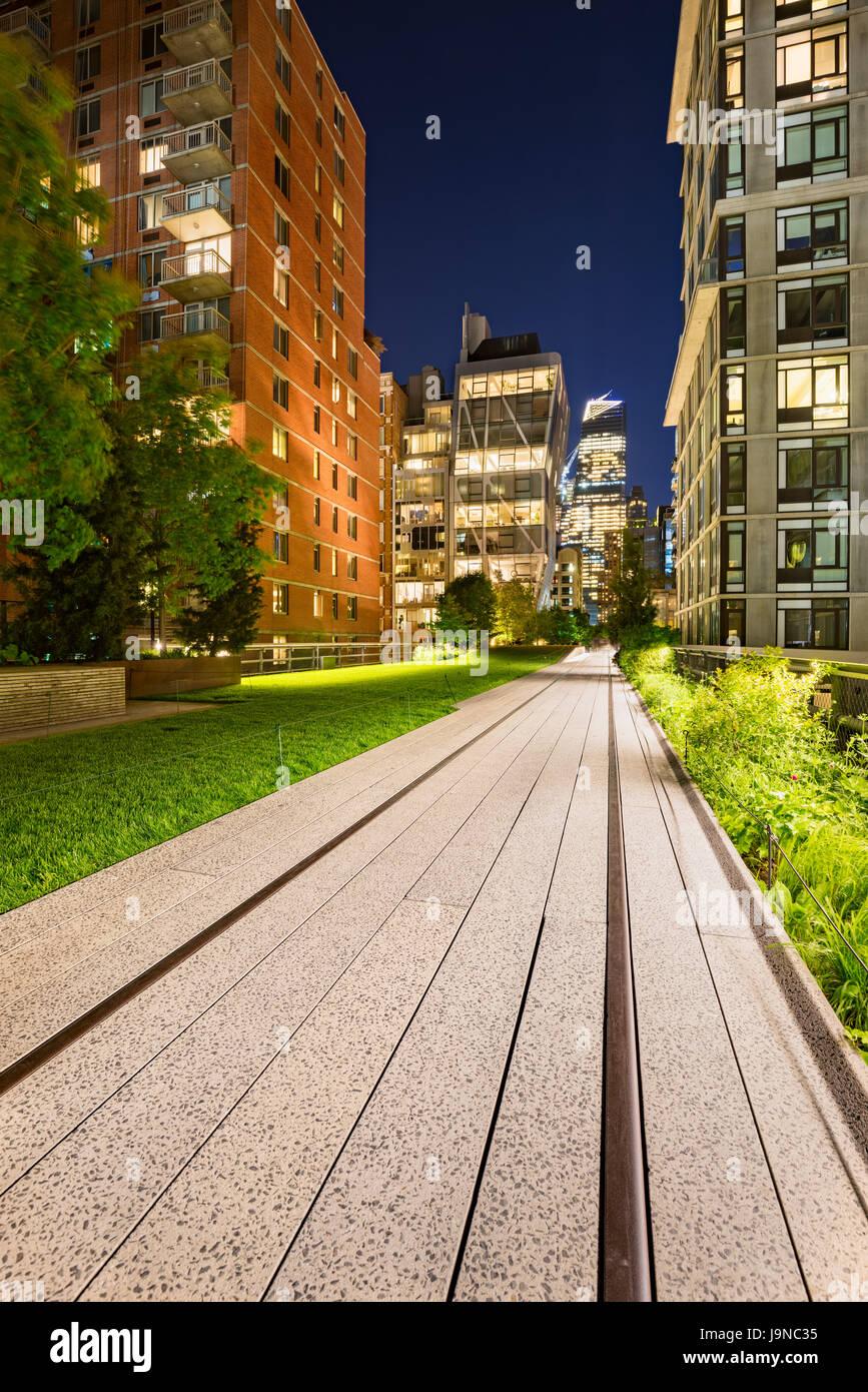 Highline promenade et ancienne voie ferrée au crépuscule avec des tours et des lumières dans Chelsea. Photo Stock