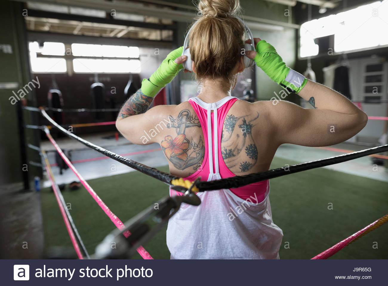 Vue arrière boxer femme tatouée à écouter de la musique avec les écouteurs en ring de boxe Photo Stock