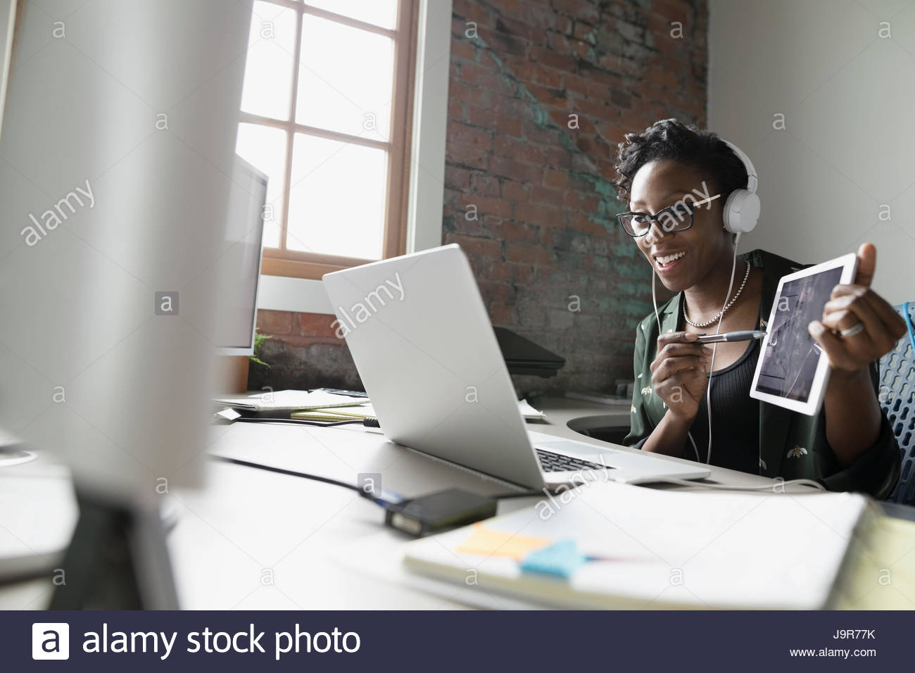 Creative businesswoman Smiling with headphones holding digital tablet et vidéoconférence à laptop in office Banque D'Images