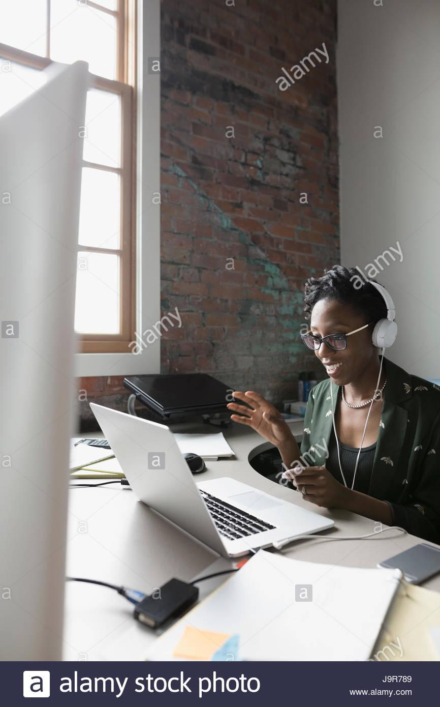 Creative businesswoman with headphones vidéoconférence à laptop in office Banque D'Images