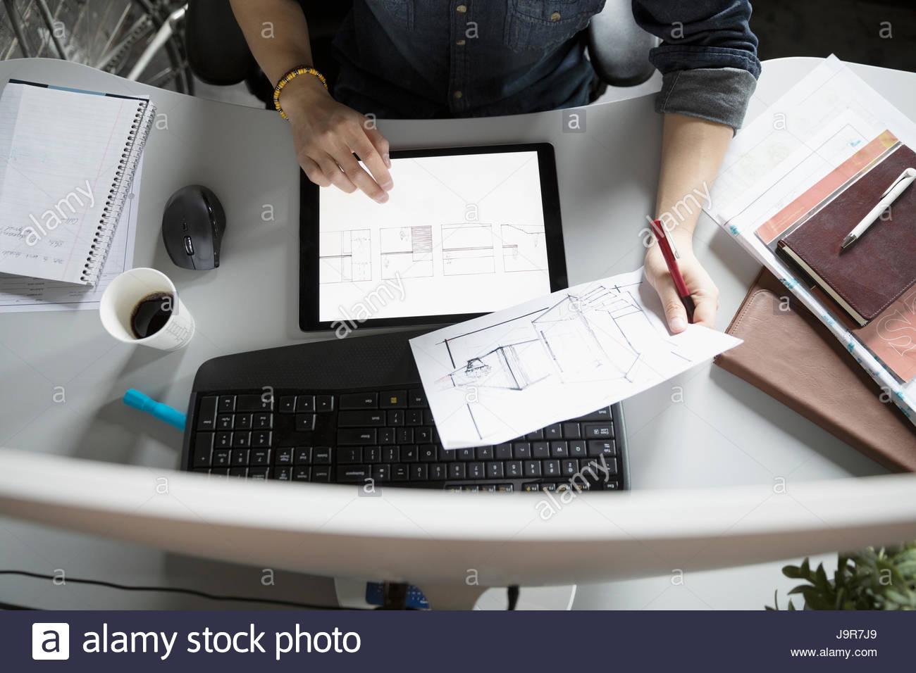 Vue de dessus male architect with digital tablet reviewing blueprints at desk Photo Stock
