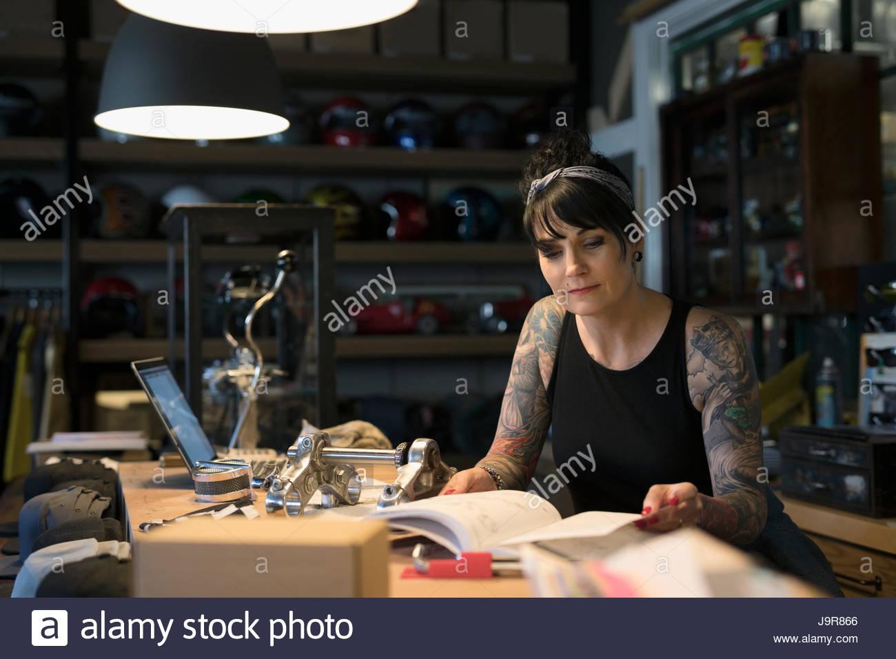 Mécanicien moto féminine à la recherche au catalogue d'un magasin de détail, derrière Photo Stock