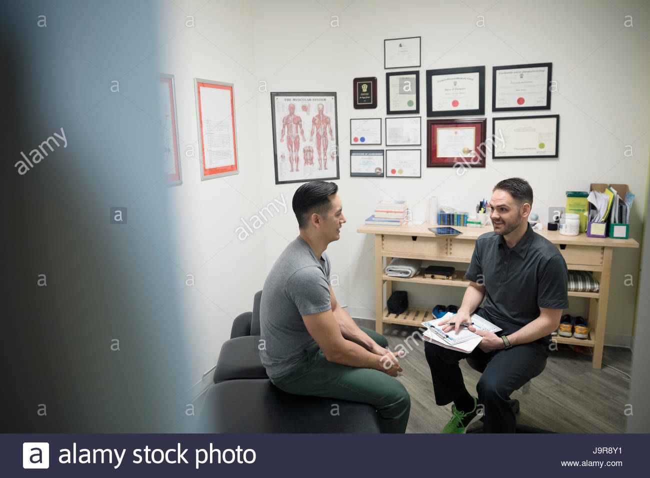 Physiothérapeute mâle parler avec client in office Photo Stock