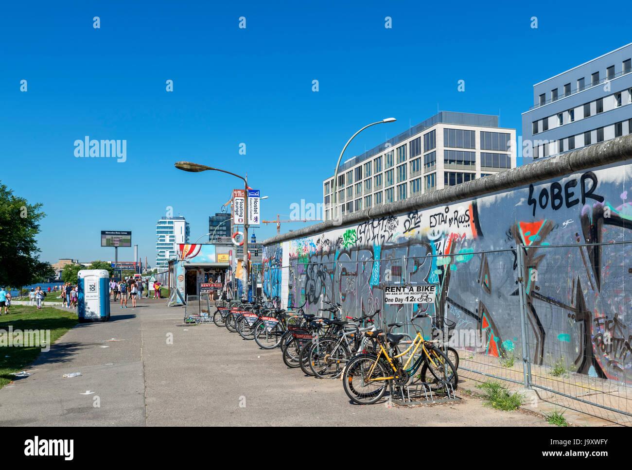 Location de vélo par une section du mur de Berlin à l'East Side Gallery, Friedrichshain-Kreuzberg, Photo Stock