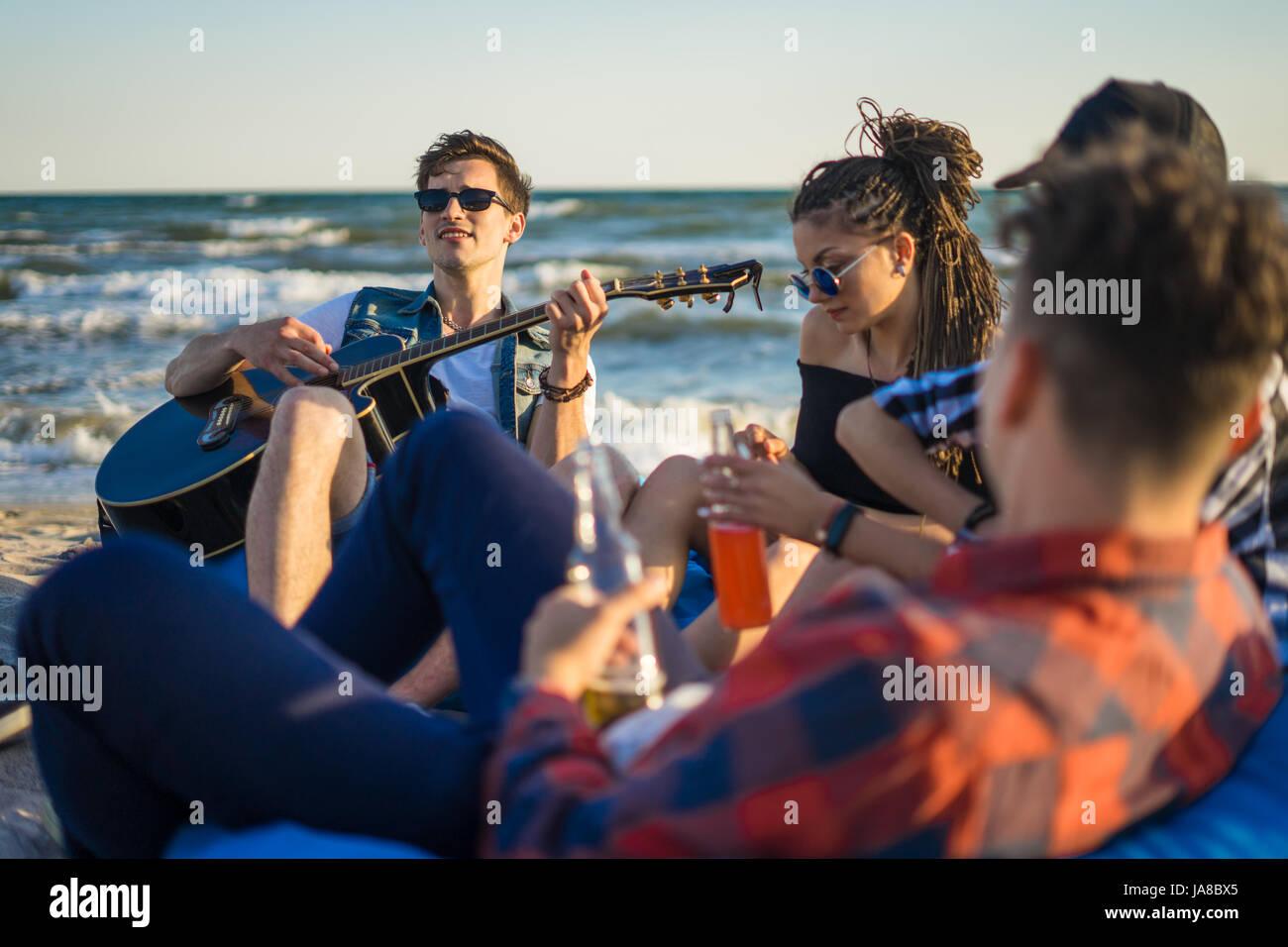 Groupe d'amis avec de la guitare et de l'alcool sur la plage partie Photo Stock