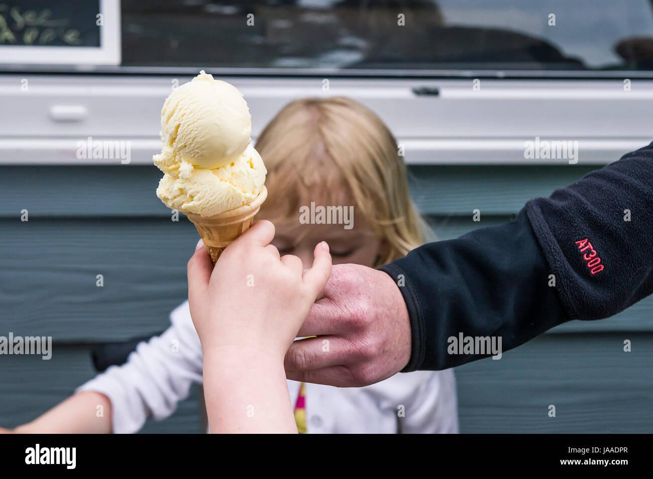 Un adulte donnant un cornet de crème glacée à un enfant. Photo Stock