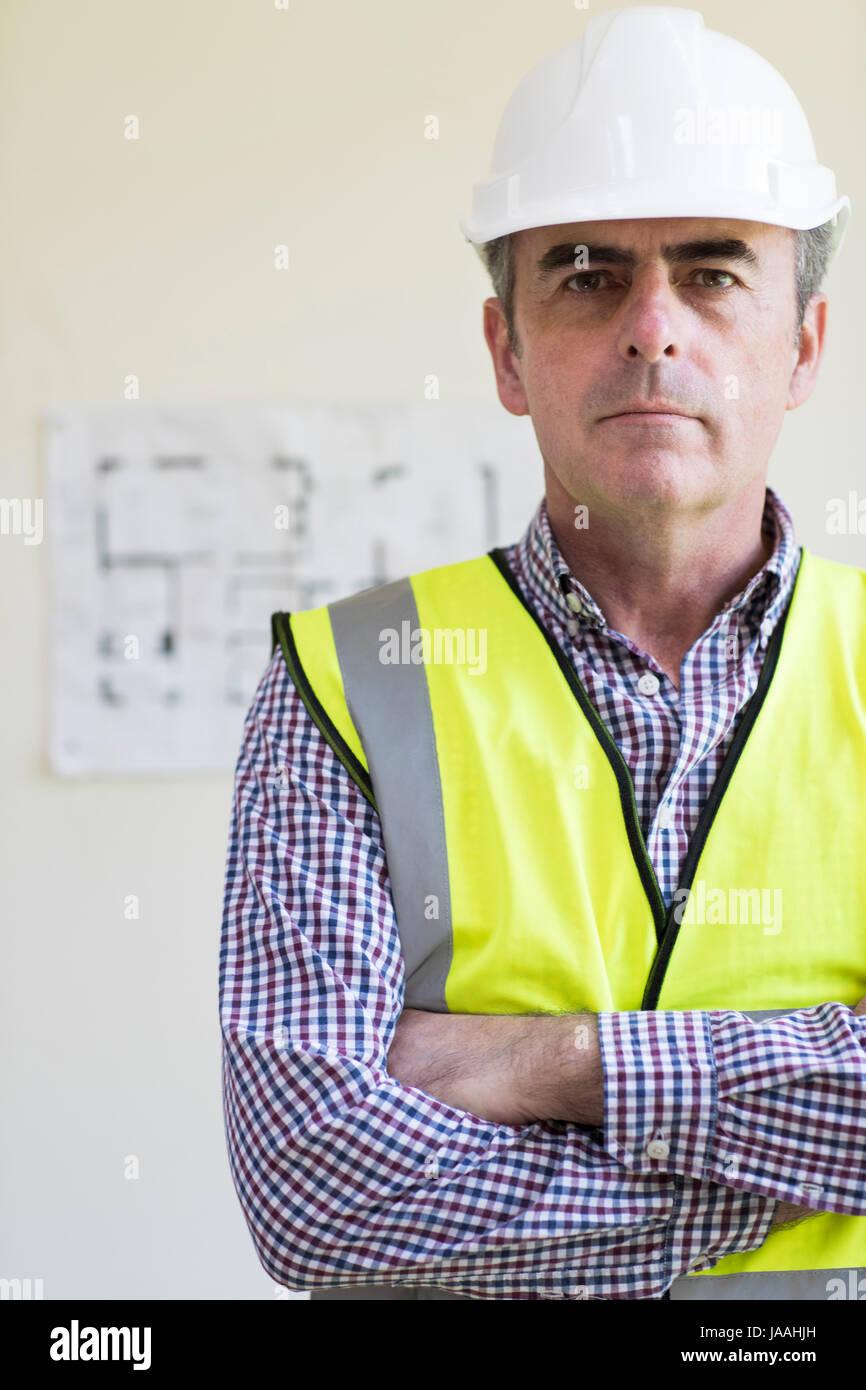 Portrait de l'architecte Wearing Hard Hat avec des plans en arrière-plan Banque D'Images