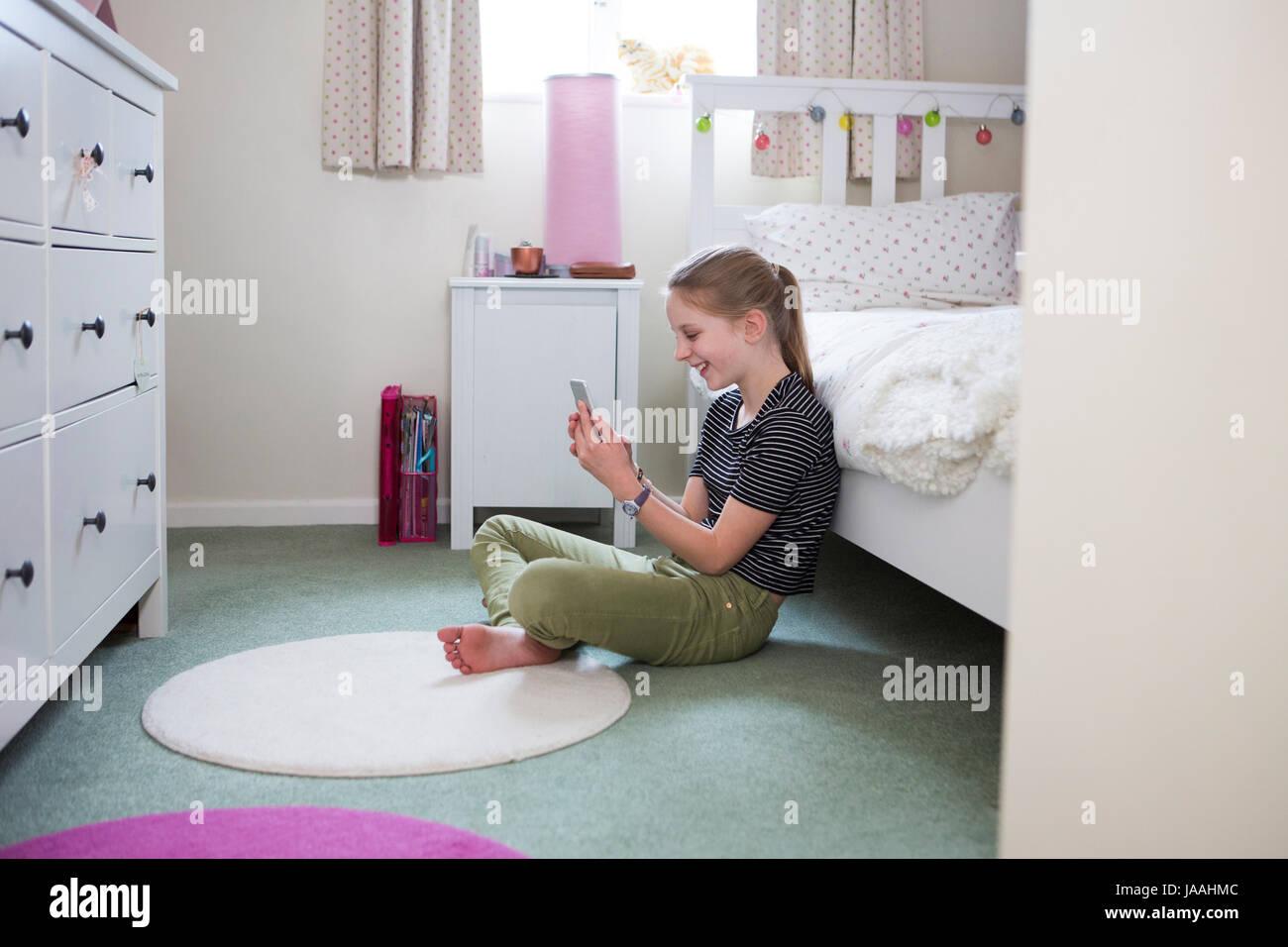 Fille assise sur le plancher de chambre à coucher en utilisant le téléphone mobile Photo Stock